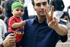 Man gestures as he carries a childduring protest in Tehran 6-18-09 from edgemalaysia flickr